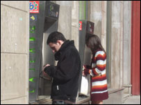 People using ATMs in Granada in Spain