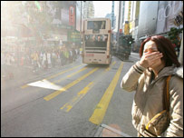 Woman covering her mouth in polluted street (Image: AFP)