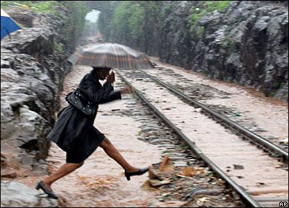 A Kenyan woman jumps over a puddle near Kibera's railway line