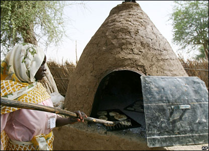 A woman bakes bread in a Darfur refugee camp