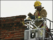 A firefighter inspecting a damaged chimney