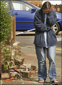 A woman rubbing her eye near damage in Folkestone