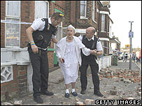 An elderly lady is helped by police officers