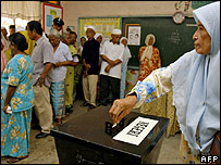 A woman casts her ballot at a polling station in Ijok, Malaysia