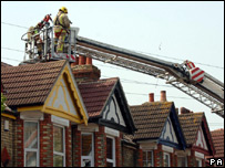 A firefighter inspecting a roof