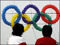 Two people observe the Olympic logo made from balloons in Beijing