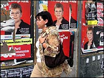 Woman walks past posters of defeated Communist candidate Marie-George Buffet