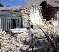 A Somali resident walks past a demolished building in Mogadishu