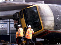 Railway workers try to remove a train carriage after the crash at Potters Bar station in 2002