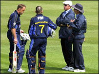 Chris Adams (left) waits with umpires George Sharp and Jeremy Lloyd (right)