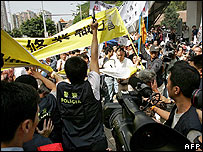 A Macau policeman fires his pistol in the air to ward off protesters - 1 May 2007