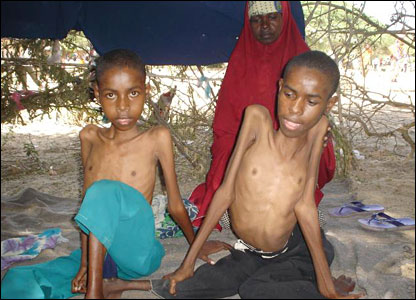 Two children and their mother after fleeing Mogadishu under a tree near Afgooye