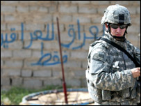A US soldier in Iraq. Behind him, the script reads: Iraq is only for Iraqis