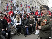 Russian World War II veteran addresses members of pro-Kremlin youth groups who sit with their party flags outside the Estonian Embassy