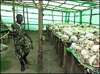 Rwandan soldier looks at remains of genocide victims