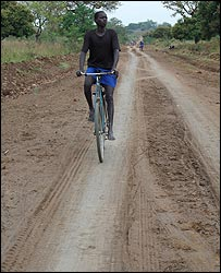 Man cycling and people walking along road that leads to Lira