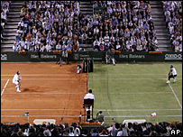 Roger Federer and Rafael Nadal play on the half-clay, half-grass court