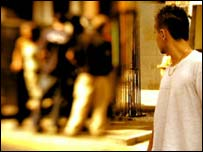 Young man looking at crowd of youths