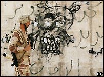 An Iraqi soldier passes skull and crossbones graffiti