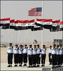 Iraqi police cadets carry Iraqi flags in front of an American flag during their graduation ceremony
