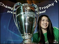 A Thai woman poses next to the UEFA Champion's League trophy