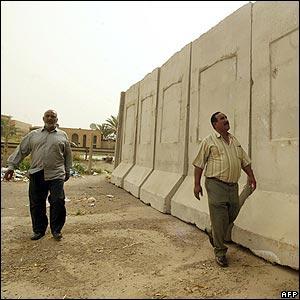 Iraqis walk past the wall
