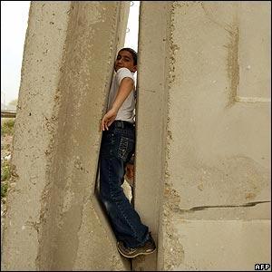 An Iraqi boy tries to pass through a gap in the wall
