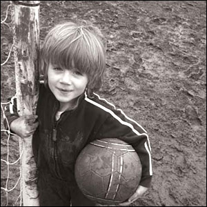 Young footballer gets ready for action in muddy conditions