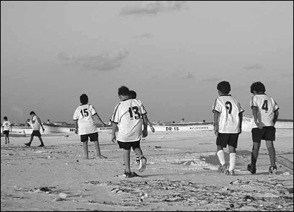 School children play football on a beach at Tulum in Mexico