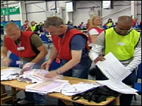 Workers inspect the damaged ballot papers