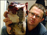 Food writer Stefan Gates holds up some raw walrus meat (muktuk) - which is a Inuit delicacy