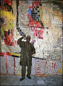 Ghanaian artist El Anatsui in front of his hanging carpet made from bottle tops