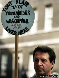 Mark Thomas with blue plaque reading 'Tony Blair '97-'07 Prime Minister and War Criminal Live Here'