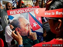 A woman shows a portrait of President Fidel Castro during the May Day parade
