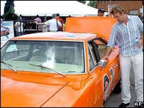 Actor John Schneider looks at a replica the General Lee