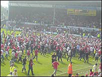 Celebrating fans stream onto the Racecourse at the final whistle