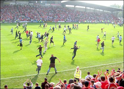Fans charge on to the pitch at the end of the game
