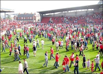 The crowd leave the pitch at the Kop end