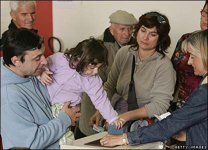 A young girl casts her father's ballot at a polling station in Melle, France