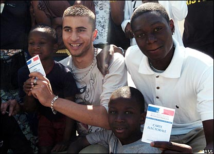 Young men pose with their electoral identity cards in Paris suburb Clichy-sous-Bois