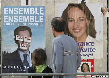 A man and a girl look at posters of the two candidates in Segolene Royal's Melle constituency