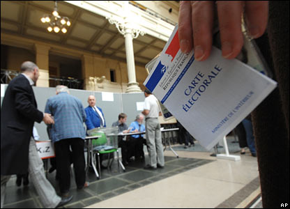 A Parisian holds his voting card as he waits his turn