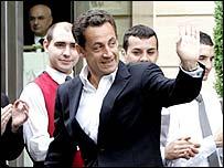 Nicolas Sarkozy waves as he leaves a Paris hotel, 7 May
