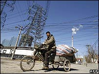 A Chinese man on a bicycle overshadowed by electricity pylons