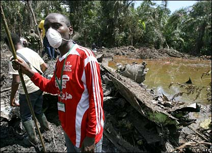 Volunteers search in a swamp after finding the nose of the plane in Mbanga Pongo