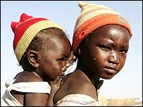 Una ni�a sudanesa desplazada carga con su hermana en Nyala, Darfur