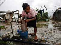 A girl washing clothes in a refugee camp in Dili