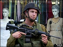Soldier outside Palestinian shop