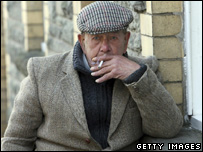 Retired book dealer Ken Jenkins smokes a cigarette outside his local pub in Hay-on-Wye, Powys