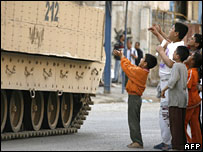 Iraqi children wait for sweets from US troops on patrol near Haifa Street, Baghdad